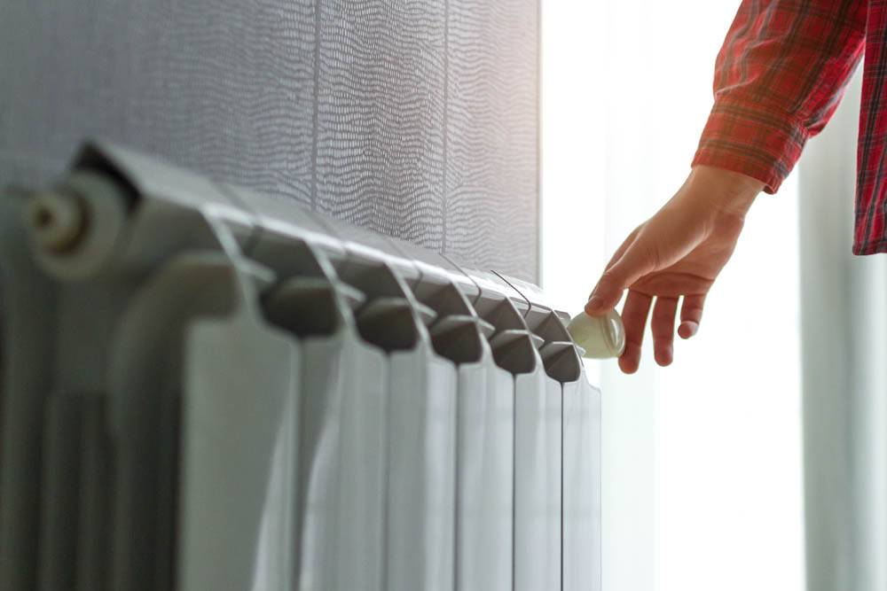 person with hand on radiator